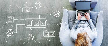 Aprobación de control de calidad con el hombre usando una computadora portátil en una silla gris moderna