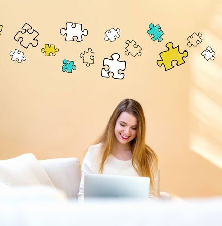 Puzzle pieces with young woman using her laptop computer at home