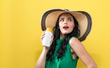 Young woman with sunscreen on a yellow background Stock Photo