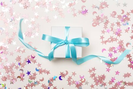 A gift box with confetti on a white background