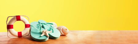 Flip flops with buoy on a yellow background Stock Photo - 124591143