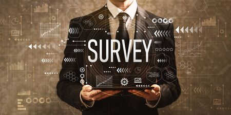 Survey with businessman holding a tablet computer on a dark vintage background