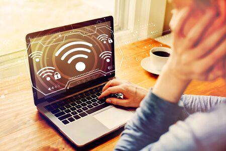 Wifi con hombre usando una computadora portátil Foto de archivo