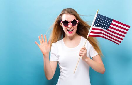 Happy young woman holding an American flag on a blue background