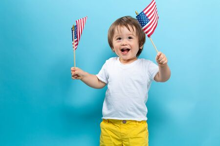 Happy toddler boy waving American flags on a blue background