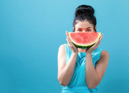 Young woman holding watermelon on a solid background