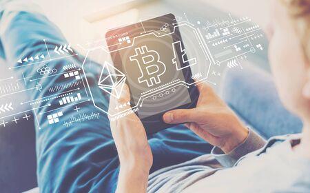 Kryptowährung - Bitcoin, Ethereum, Litecoin mit einem Mann, der ein Tablet in einem Stuhl verwendet