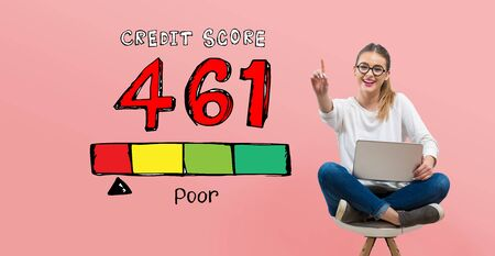 Poor credit score theme with young woman using her laptop Banco de Imagens