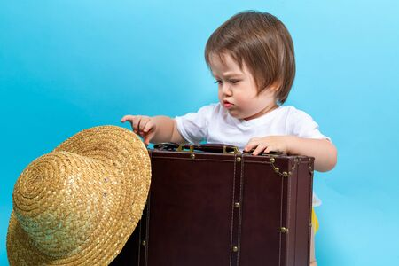 Toddler boy travel theme with a suitecase and a hat on a blue background Banco de Imagens
