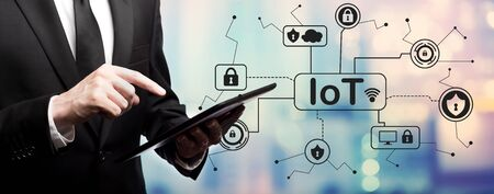 IoT security theme with businessman using his tablet computer