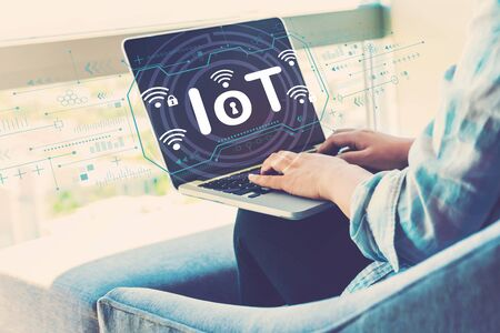 IoT theme with woman using her laptop in her home office