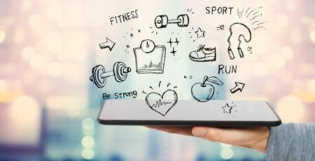 Fitness and diet with man holding a tablet computer Stock Photo - 125903665