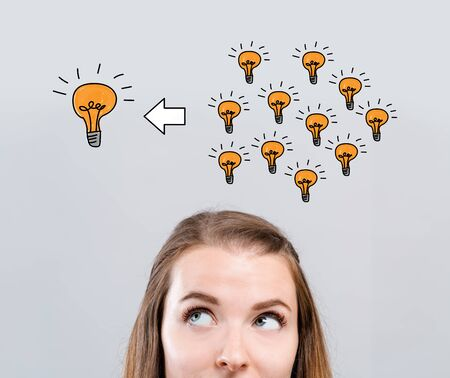 Many small ideas into one big idea with young woman looking upwards