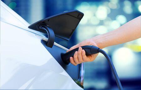 Persona cargando un vehículo eléctrico en la ciudad. Foto de archivo