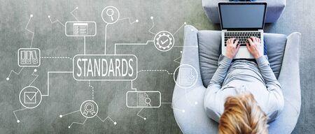 Standaardgoedkeuring van de kwaliteitscontrole met een man die een laptop gebruikt in een moderne grijze stoel