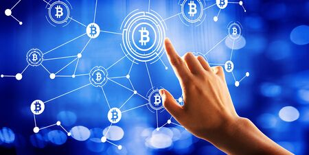 Bitcoin theme with hand pressing a button on a technology screen Foto de archivo
