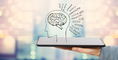 Brain illustration with man holding a tablet computer Фото со стока