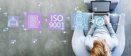 ISO 9001 with man using a laptop in a modern gray chair