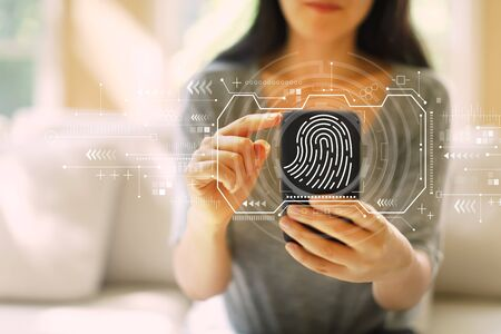 Fingerprint scanning theme with woman using her smartphone in a living room Stockfoto