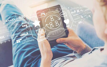 Social-Media-Thema mit einem Mann, der ein Tablet in einem Stuhl verwendet Standard-Bild