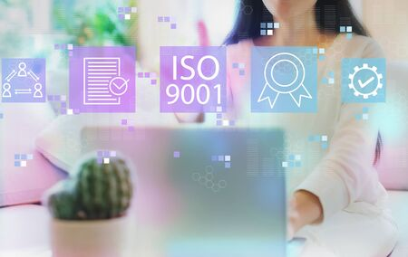 ISO 9001 with woman using her laptop in her home office Stock Photo