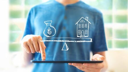 House and money on the scale with young man using a tablet computer Stock Photo