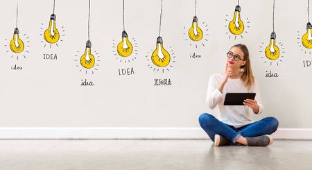 Idea light bulbs with young woman holding a tablet computer Banco de Imagens