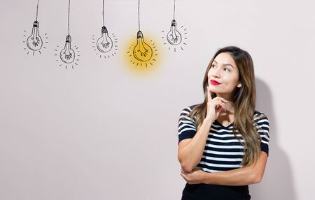 Idea light bulbs with young businesswoman in a thoughtful face Фото со стока - 127114172
