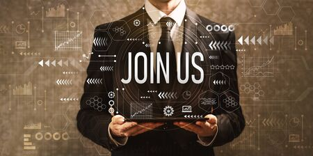 Join us with businessman holding a tablet computer on a dark vintage background Banque d'images
