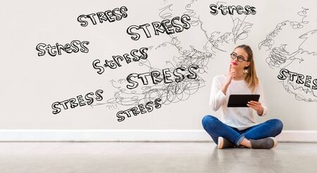 Stress theme with young woman holding a tablet computer Imagens