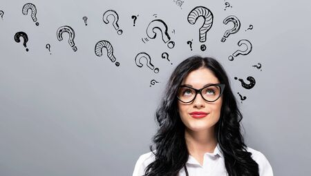 Question marks with young businesswoman in a thoughtful face Stock Photo