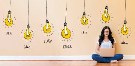 Idea light bulbs with young woman using a laptop computer Banco de Imagens
