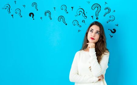 Question marks with young woman in a thoughtful face Stockfoto