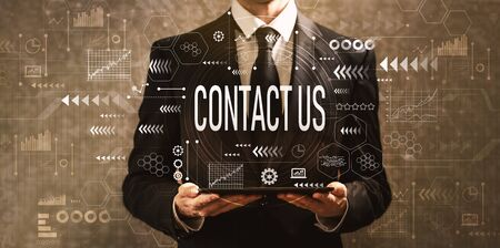 Contact us with businessman holding a tablet computer on a dark vintage background