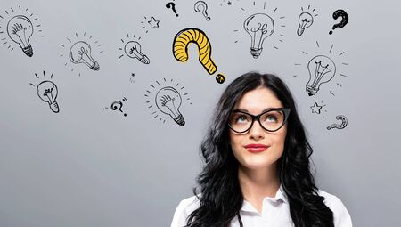 Question with light bulbs with young businesswoman in a thoughtful face