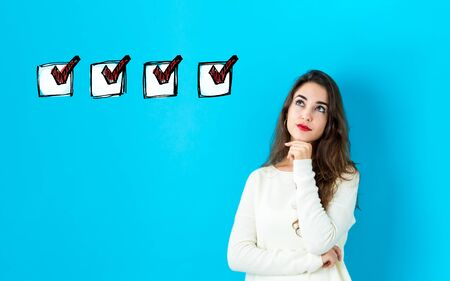 Checklist with young woman in a thoughtful face Banco de Imagens