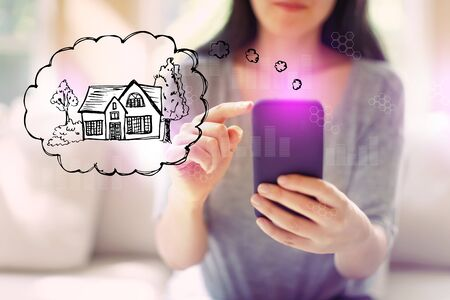 Dreaming of new home with woman using her smartphone in a living room