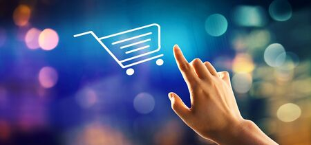 Online shopping theme with hand pressing a button on a technology screen Banco de Imagens