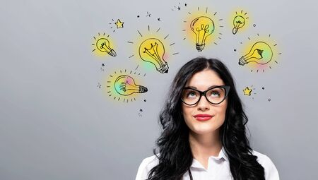 Idea light bulbs with young businesswoman in a thoughtful face Banco de Imagens - 127780558