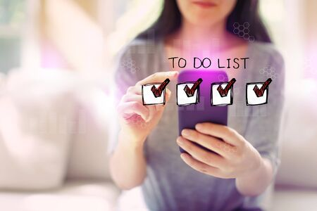 To do list with woman using her smartphone in a living room