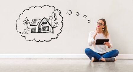 Dreaming of new home with young woman holding a tablet computer Stock Photo