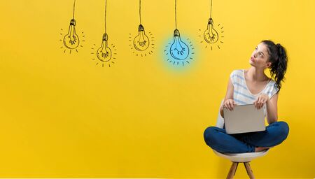 Idea light bulbs with young woman using a laptop computer Stock Photo - 127936670