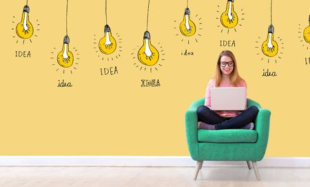 Idea light bulbs with young woman using her laptop in a chair Stock Photo