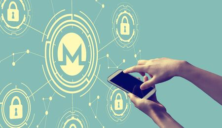 Monero cryptocurrency security theme with person holding a white smartphone