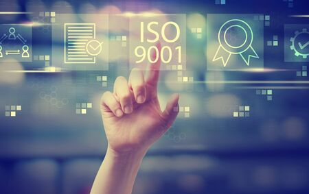 ISO 9001 with hand pressing a button at night