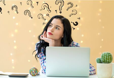 Question marks with young woman using a laptop