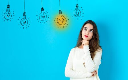 Idea light bulbs with young woman in a thoughtful face Banco de Imagens - 128615357
