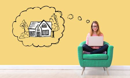 Dreaming of new home with young woman using her laptop in a chair