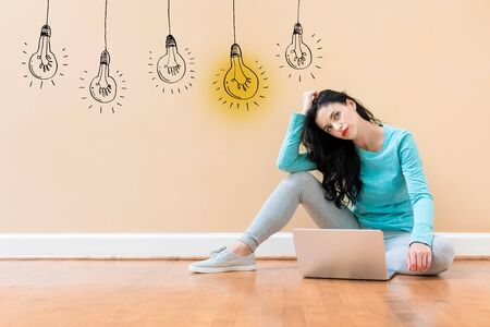 Idea light bulbs with young woman using a laptop computer Stock Photo - 128550152