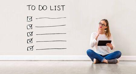 Lista rzeczy do zrobienia z młodą kobietą trzymającą komputer typu tablet Zdjęcie Seryjne